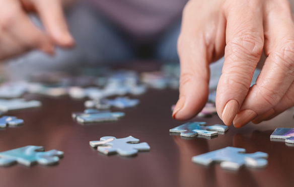 Female hands putting together a puzzle on a wooden table.