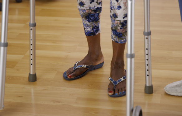Close up of a women's feet as she is using a walking frame for support.