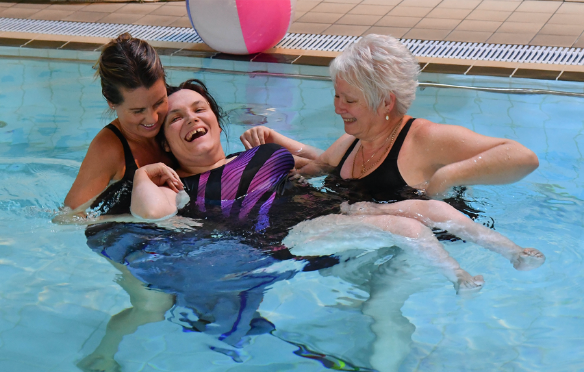 Two female's are supporting a female by holding her in the swimming pool. All three women are smiling in the pool.