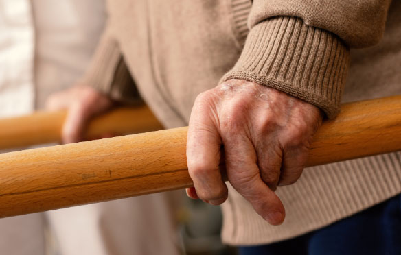 Male hands holding on to wooden rails for support