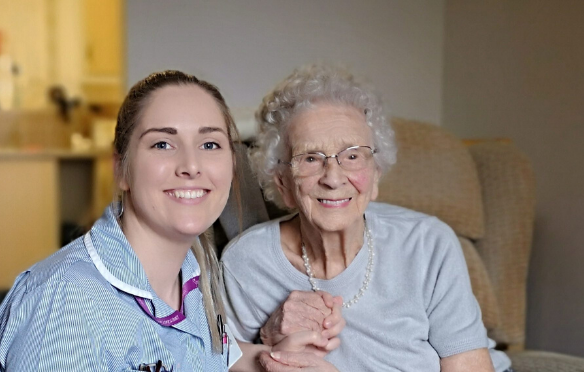 A female nurse sat smiling next to a older lady who is also smiling, the nurse is holding the ladies hands.