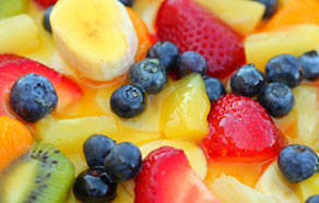 Image of fruit zoomed in, it includes blueberries, pineapple and red berries.