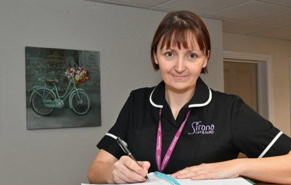 Female nurse leaning on a desk inside a residential living home, she is looking directly at the camera smiling wearing her nursing uniform and Sirona badge. The nurse is holding a pen to paper. The background shows images of a bicycle and chairs.