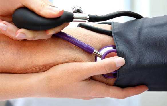 A hand of a health professional using a stethoscope on a patients arm.