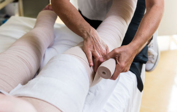 A picture of a healthcare employees hands bandaging a patients legs
