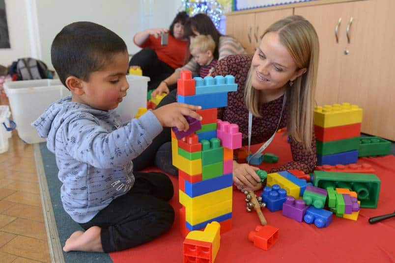 A speech and language therapist smiles at a toddler as he builds a tower using colourful bricks