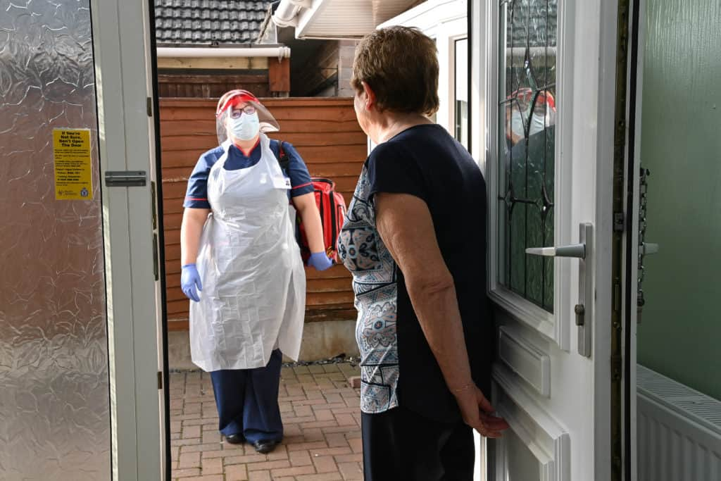 Woman greats a Community nurse wearing PPE at her door