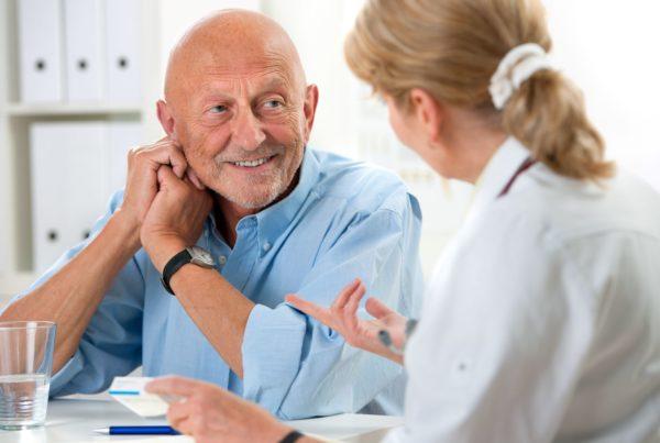 Man sat at desk in conversation with female nurse